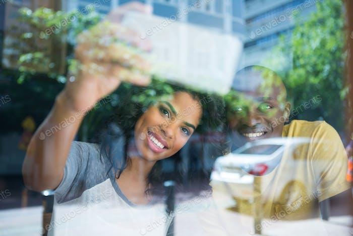 Couple taking selfie in coffee shop seen through window