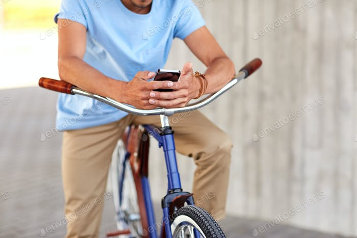close up of man with smartphone and bike on street