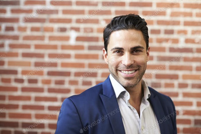 Portrait Of Smiling Mature Businessman Standing Against Brick Wall In Modern Office