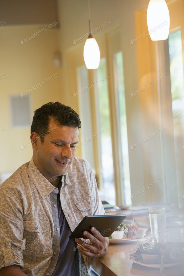 Ein Mann, der ein digitales Tablet benutzt.