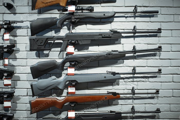 Rifles on showcase in gun shop closeup, nobody