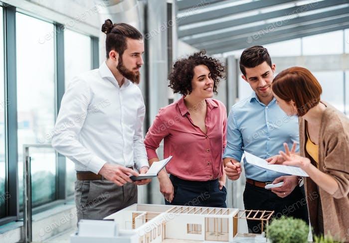 Gruppe junger Architekten mit Modell eines Hauses, das im Büro arbeitet, im Gespräch.