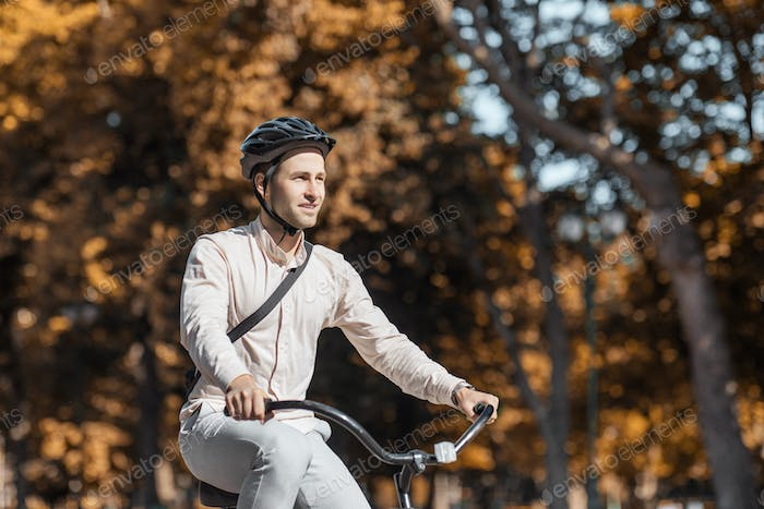 Handsome hipster cycling through city. Guy on bike in helmet ride to work