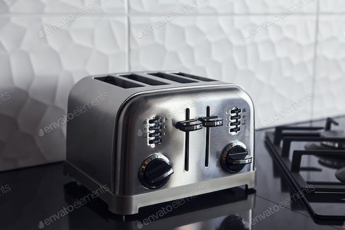 Nahaufnahme eines silberfarbenen Toasters, der in der Küche auf einem Gasherd steht