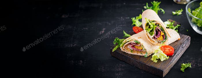 Fresh tortilla wraps with ham beef and fresh vegetables on wooden board