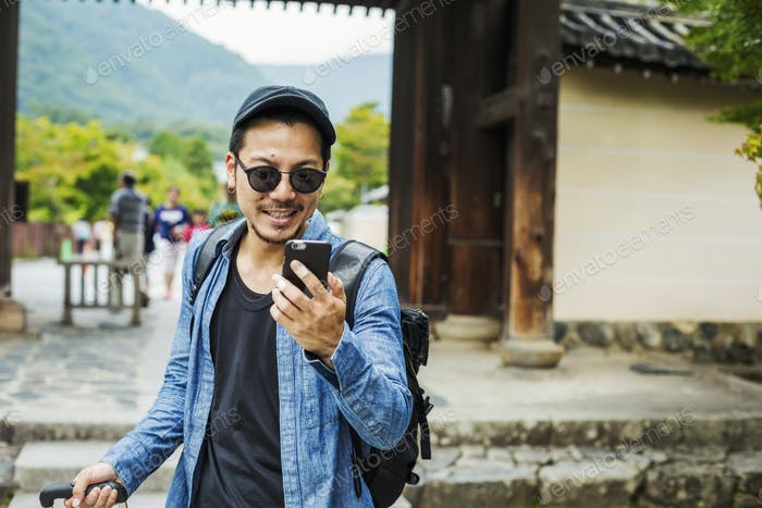 A man in sunglasses looking at his smart phone.