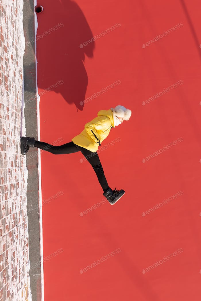 Fashionable winter portrait of a woman walking wide against a red wall