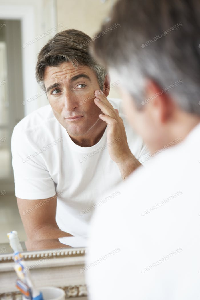 Man Looking At Reflection In Bathroom Mirror