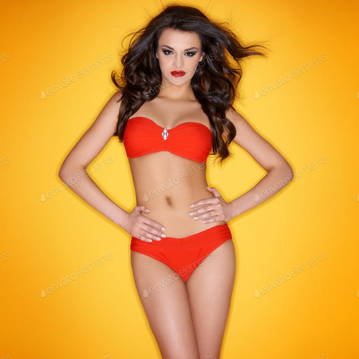 Sexy brunette posing in red bikini on yellow