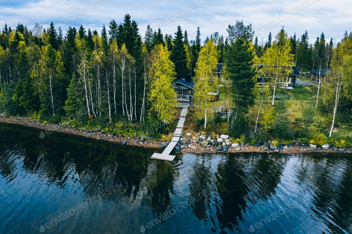 Aerial top view of log cabin or cottage with sauna in spring forest by the lake in Finland
