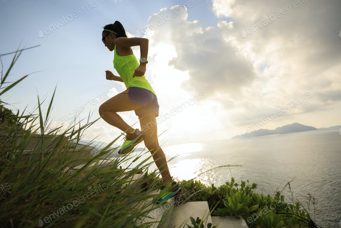 Woman runner running upstairs on seaside mountain trail