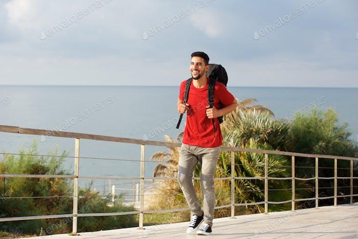 glücklicher junger männlicher Wanderer mit Rucksack am Meer