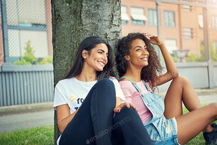 Diverse pair of cute women sitting under tree