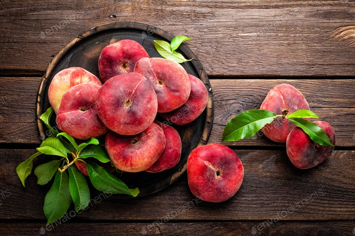 Pfirsich-, Saturn- oder Donut-Pfirsiche mit Blättern