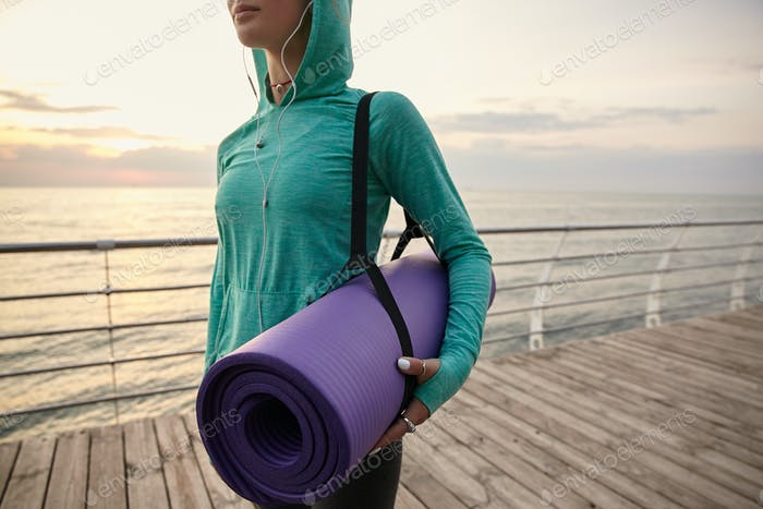 Portrait of young woman walking at the seaside, holding a purple yoga mat, going to practicing yoga