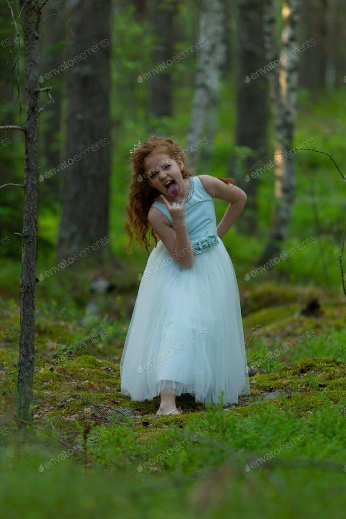 Kleine emotionale Mädchen geht in einem Sommerwald in einem Kleid