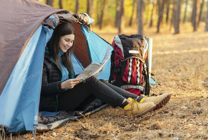 Cheerful girl sitting in tent and looking at map