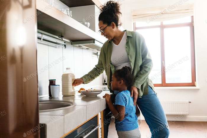 Happy mother preparing breakfast with her daughter in home kitchen