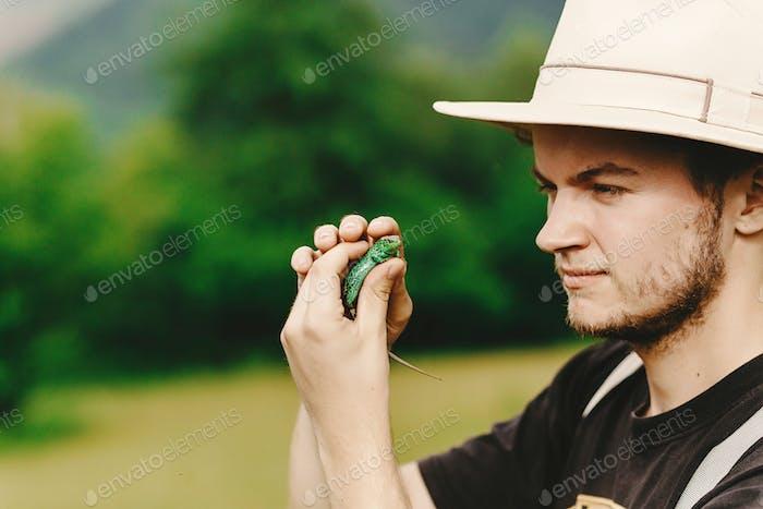 Reisender hält grüne Eidechse in der Hand