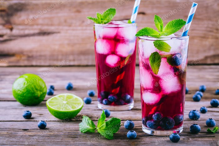 Blueberry ice lemonade with lime and mint in glasses