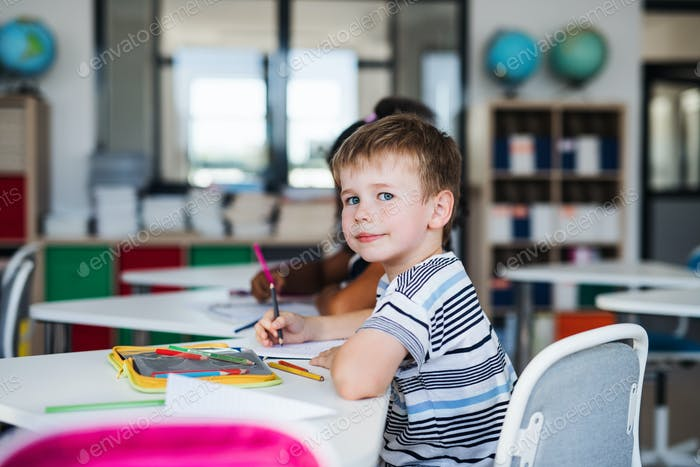 A small school boy sitting at the desk in classroom, writing