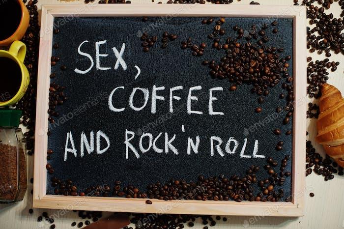 Sex, coffee and rock n roll. Words on blackboard flat lay.