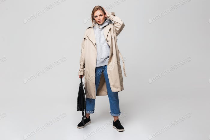 Young beautiful woman in trench coat and jeans holding black backpack in hand