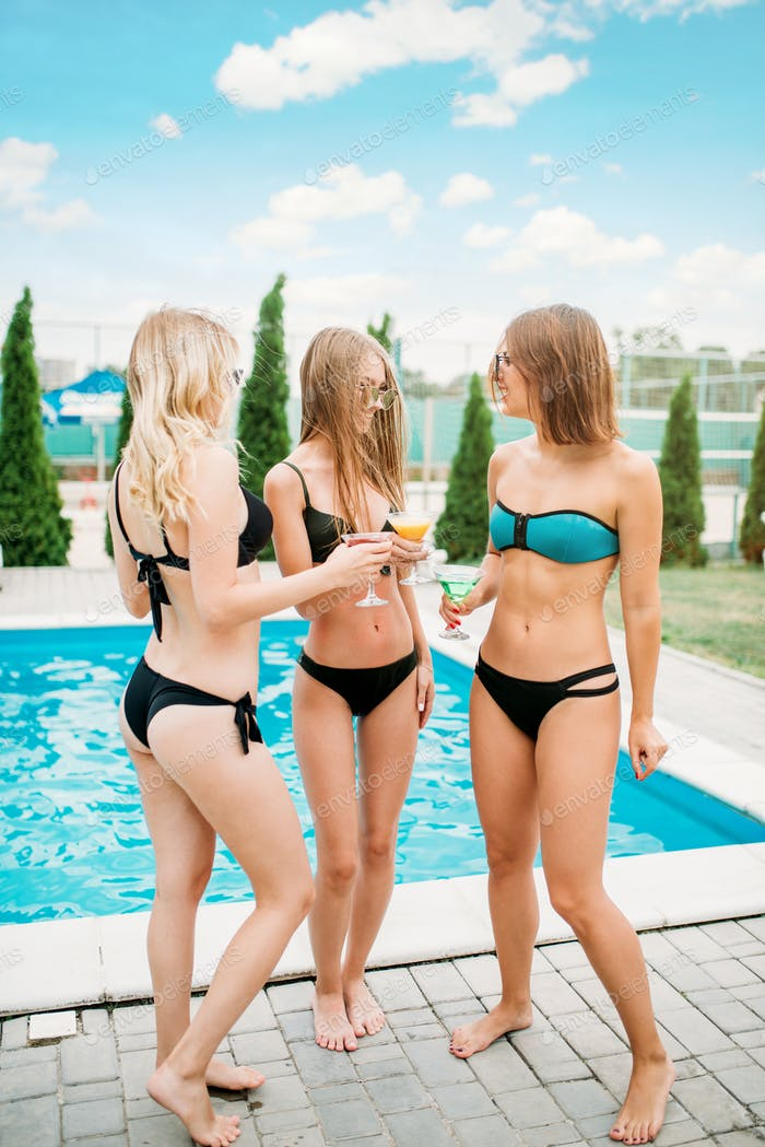 Sexy girls drinks cocktails near the swimming pool