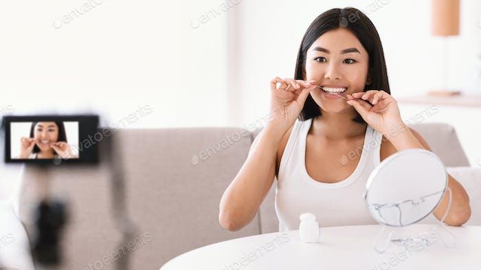 Junge asiatische Dame mit Zahnseide Aufnahme vlog