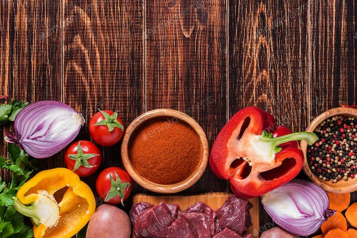 Ingredients for goulash or stew cooking: raw meat,herbs,spices,vegetables on dark wooden background.