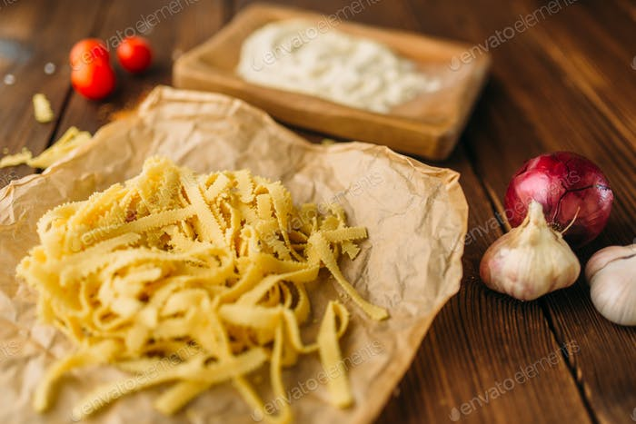 Uncooked pasta on wooden table closeup, nobody