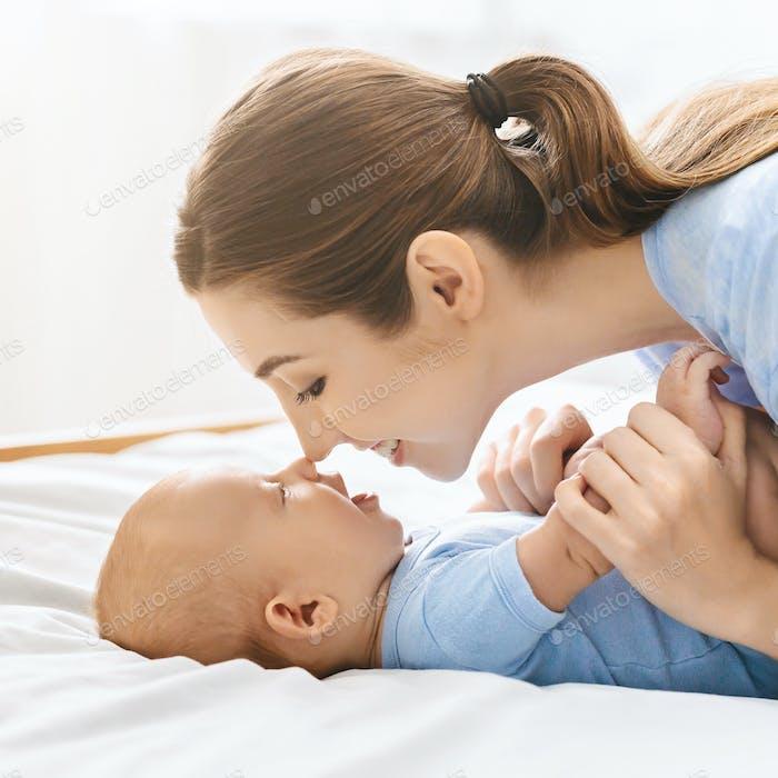 Mutter und Baby berühren Nasen im Bett, Spaß zusammen