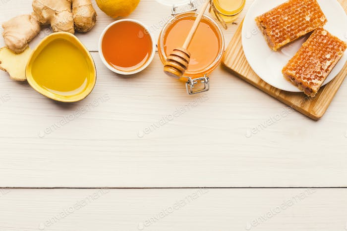 Various types of honey on wooden background, top view