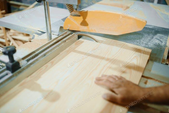 Tischler am PC arbeitet mit Holzbearbeitungsmaschine