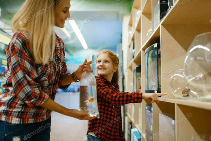 Mother with daughter choosing aquarium, pet store