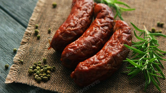 Rosemary and pepper near whole sausages