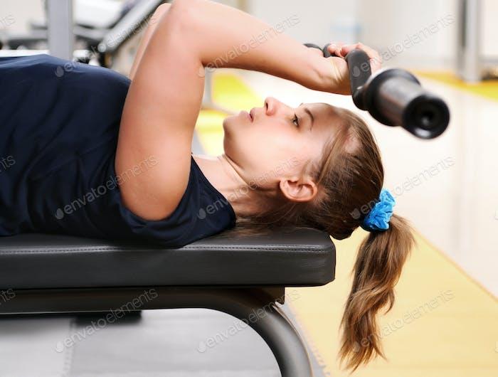 Girl in sportswear lying training with dumbbells