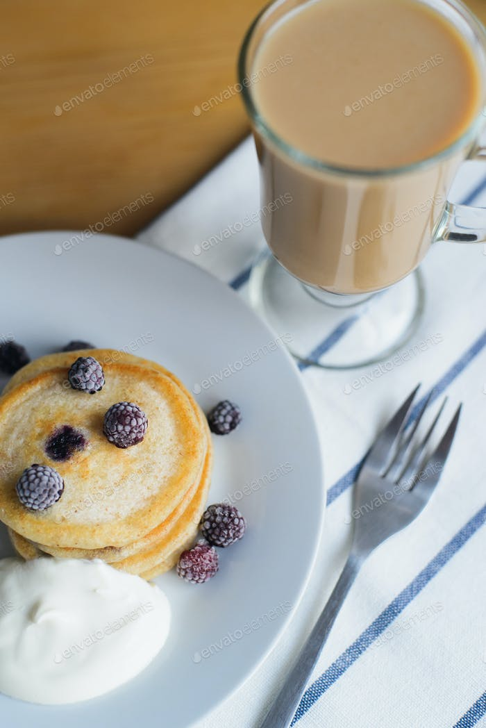 oladyi or pancakes with black raspberry with smetana on plate