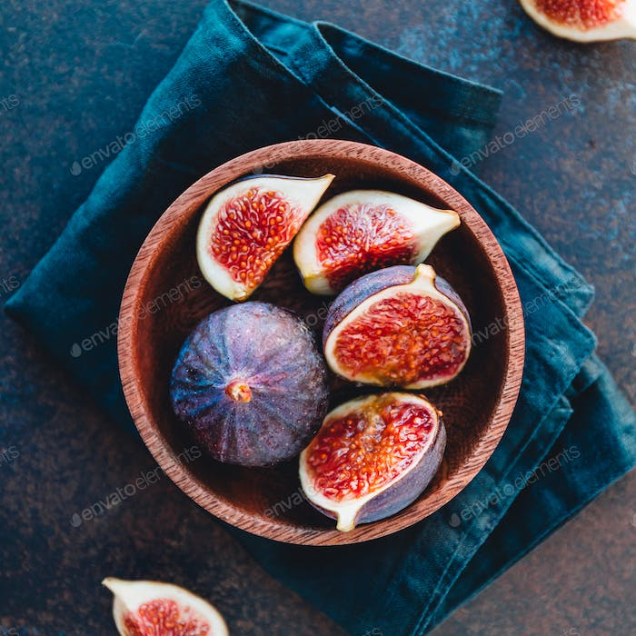 Top view of ripe quartes figs in a wooden small bowl on a table.