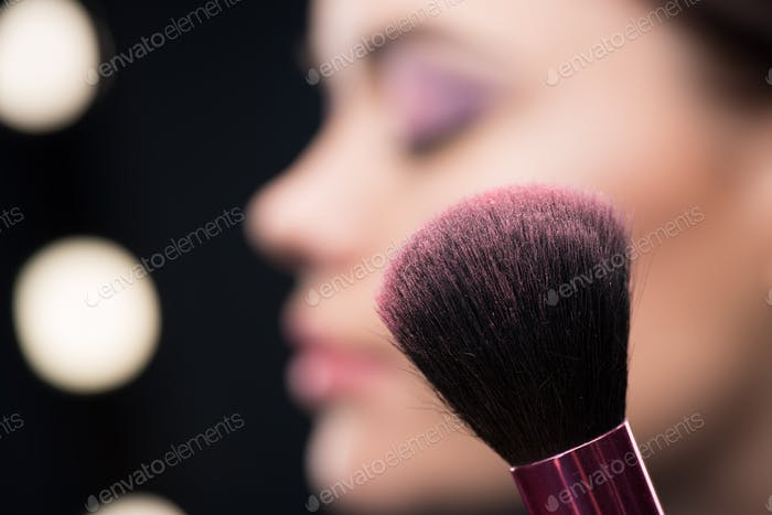 Close-up view of make-up brush with pink blusher on it