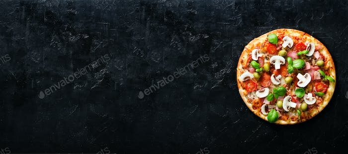 Fresh italian pizza with mushrooms, ham, tomatoes, cheese, olive, basil on black concrete background