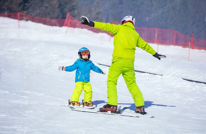 Instructor teaching little boy to ski