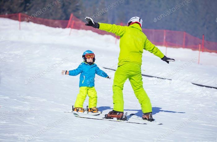 Instruktor lehrt kleinen Jungen zum Skifahren