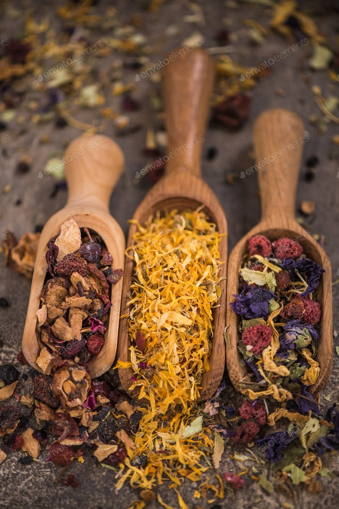 Assorted loose aromatic herbal tea on wooden spoons