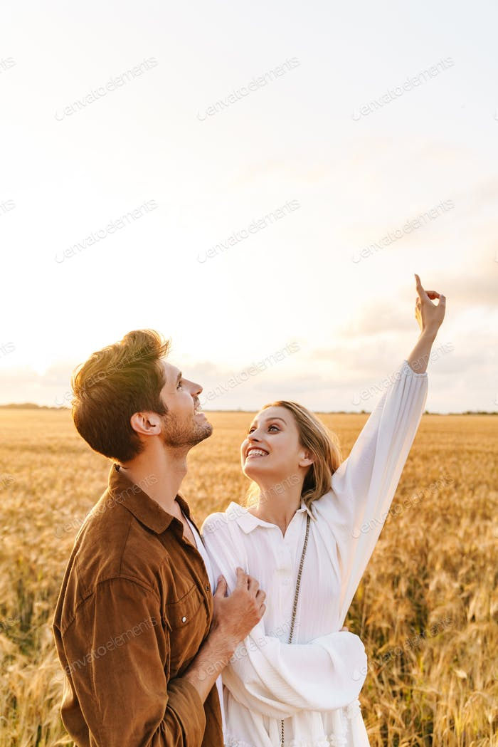 Image of young couple gesturing finger upward at sky in golden field