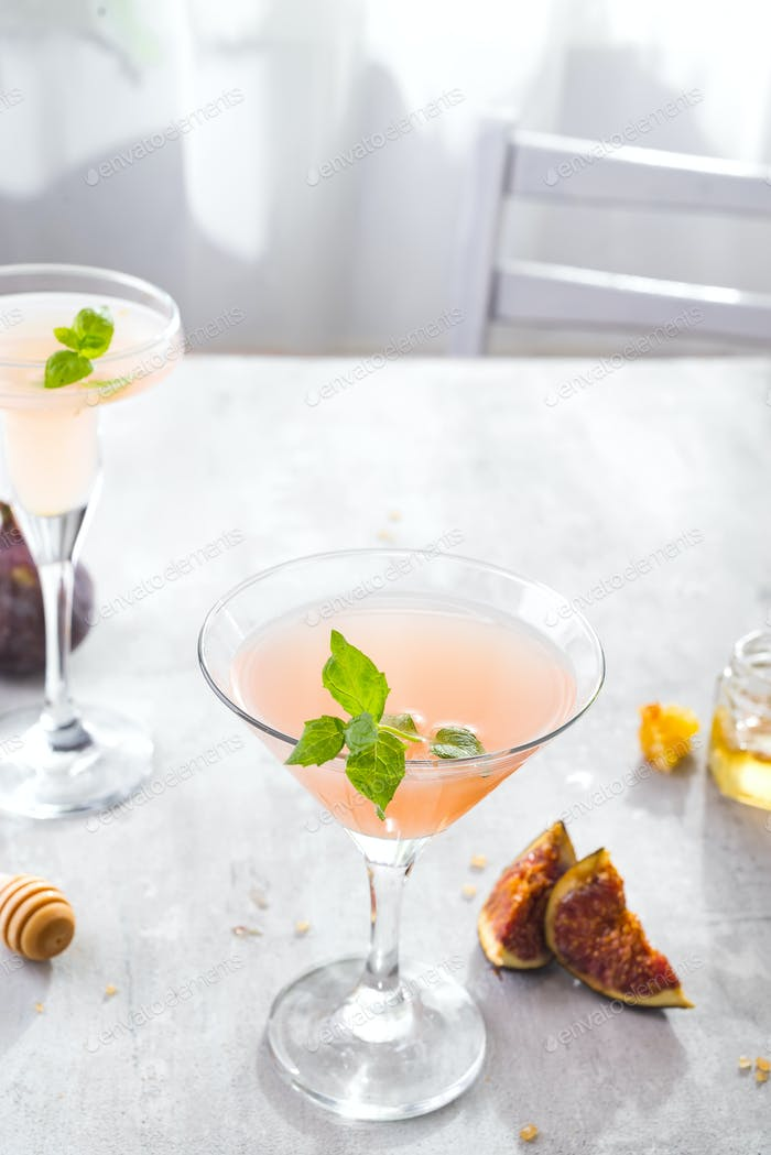 Jack Rose Cocktail with figs and honey on light background over windows, flat lay with copy space