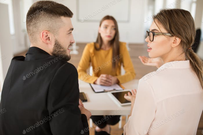 Young businessman and businesswoman thoughtfully discussing new