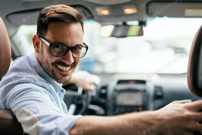 Handsome businessman driving a car