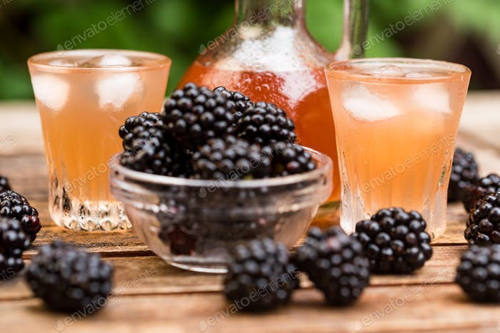 Fresh blackberries and liqueur on wooden table
