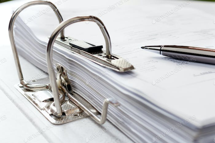 Pen on file folder with documents, storage of contracts. selective focus.